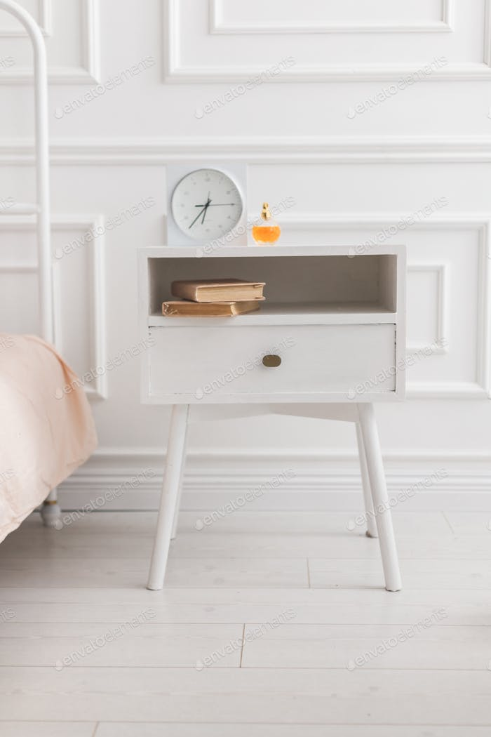 White wooden nightstand with alarm clock and books. Scandinavian style white interior