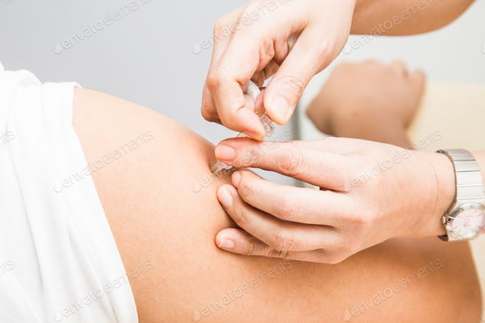 Medical doctor injecting vaccine into the arm of a patient