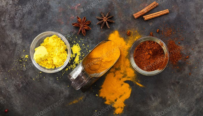 Colorful spices and an old metal scoop on metal rusty background, top view