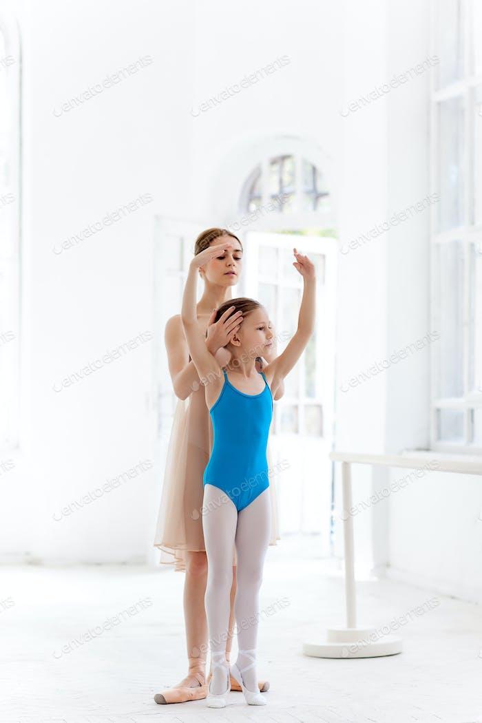 Die kleine Ballerina posiert bei Ballettstange mit persönlicher Lehrerin im Tanzstudio