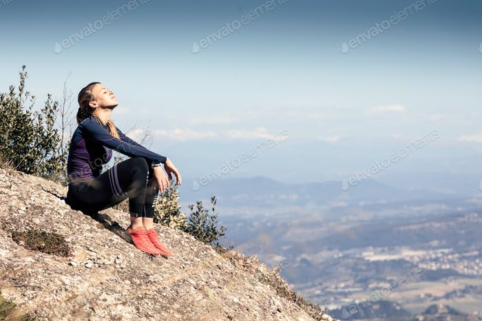 Trail runner sitting and taking a break while looking landscape