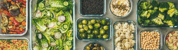 Verschiedene gesunde vegane oder vegetarische Gerichte in Behältern, breite Zusammensetzung