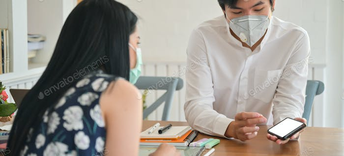Male insurance agent wearing a mask is introducing coronavirus insurance package with smartphone.