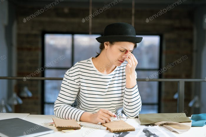 Tired young female designer in hat and striped pullover trying to concentrate