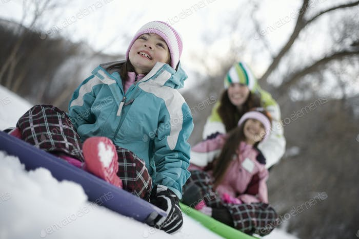 Zwei Kinder spielen auf Schlitten, auf dem Schnee.