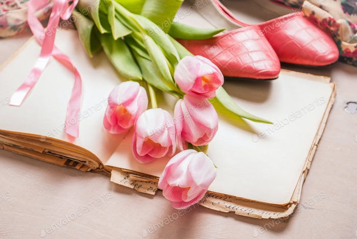 Pink tulips and blank book with women`s shoes over white wooden table. Spring chic background