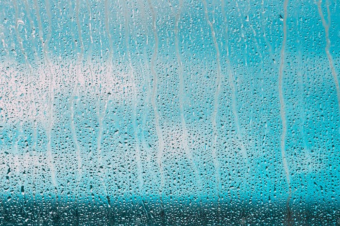 Drops Of Water Or Rain On Wet Glass Background. Moody Photo In Cold Blue Color