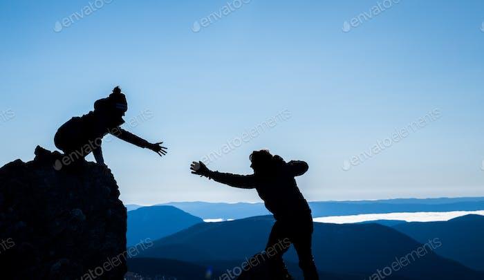 paar in silhouetten helfen einander für sucess
