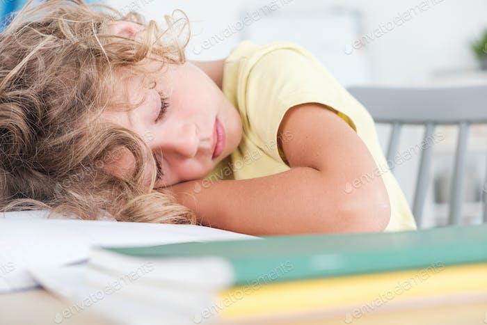 Close-up of sleeping boy while doing homework on desk
