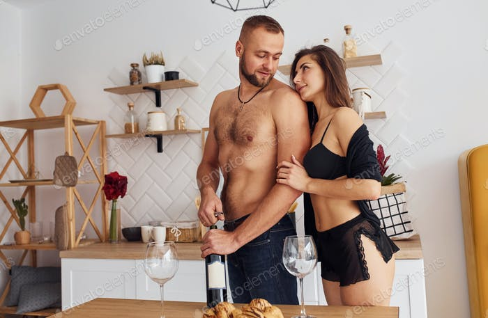 Woman in sexy black lingerie with her husband on the kitchen