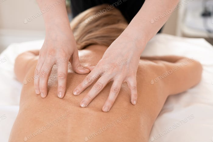 Massaging naked back of woman on table