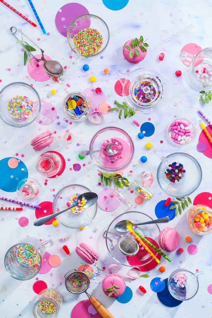 Partyzubehör in Glas Teetassen. Sprinkles, Konfetti, Bonbons, Makronen und Geburtstagskerzen auf einem