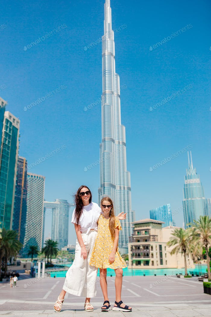 Happy family walking in Dubai with skyscrapers in the background