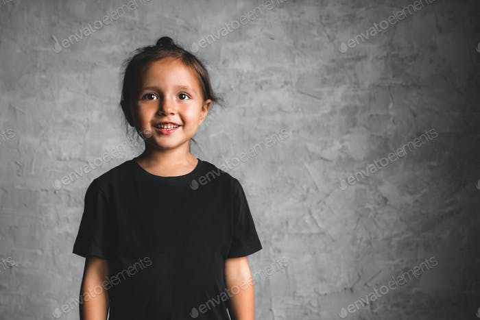 Little girl on a gray background. Portrait in beautiful colors