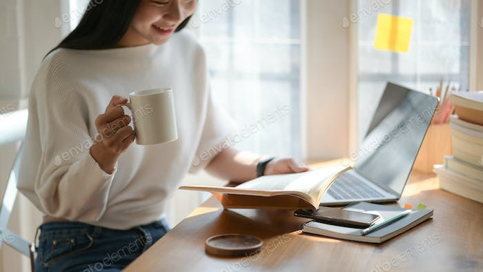 A picture of a young student holding a cup of coffee and reading in a beautiful light cafe.