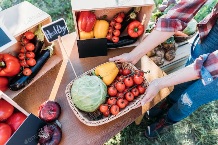 cropped shot of farmer selling healthy organic locally grown vegetables on stall