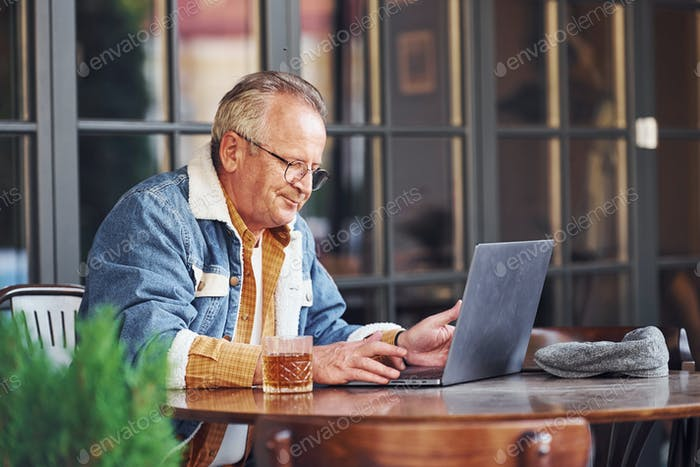 Stilvolle Senior in modischer Kleidung und in Brille sitzt im Café und arbeitet mit Laptop