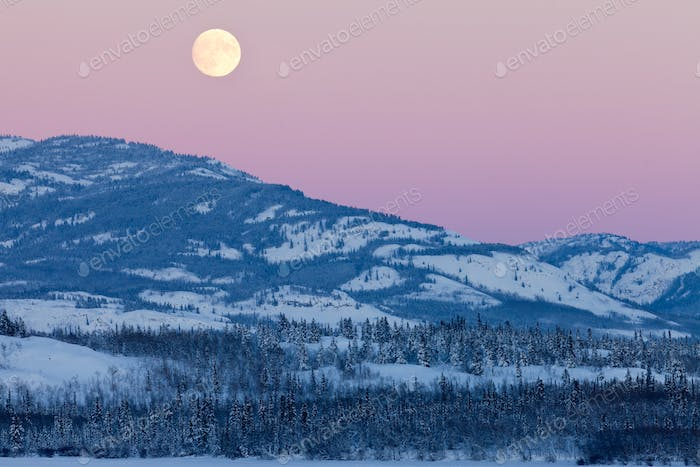 Yukon Canada winter landscape and full moon rising