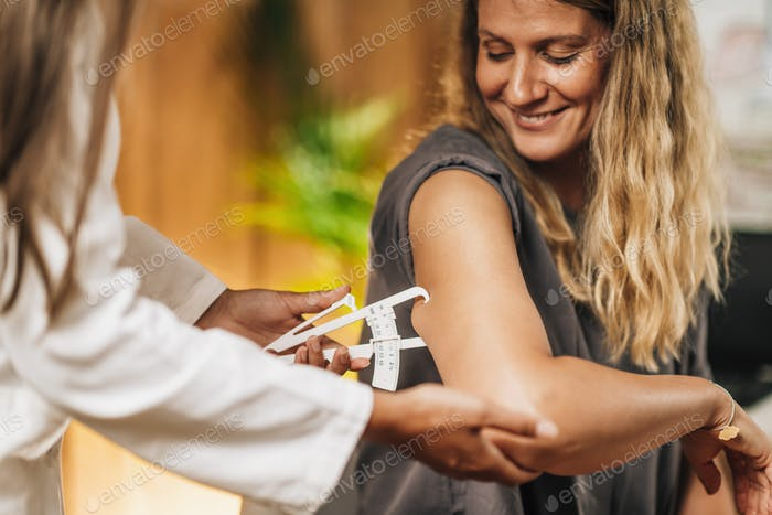 Body Fat Test, Using Caliper on the Female Patient's Arm