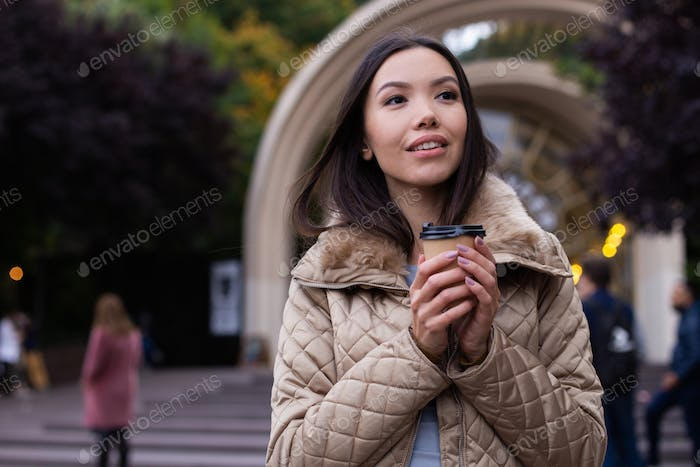 Young attractive casual woman in down jacket with coffee to go dreamily looking away on city street