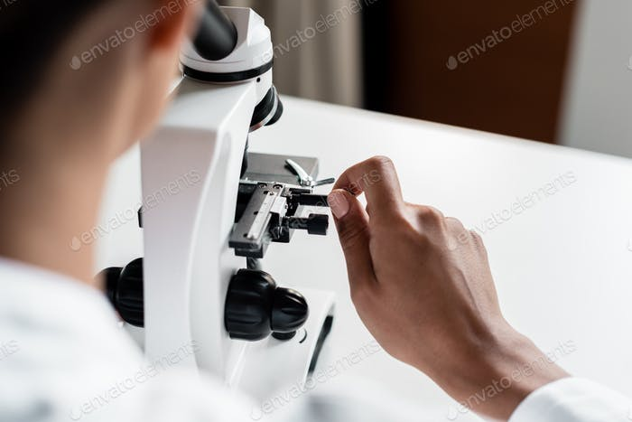 Cropped shot of professional chemist working with microscope in laboratory