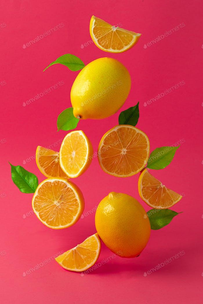 Zitronen schweben vor hellrosa Hintergrund in der Luft