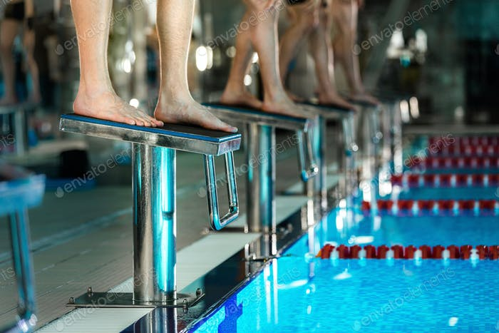 Men's feet standing on starting blocks preparing