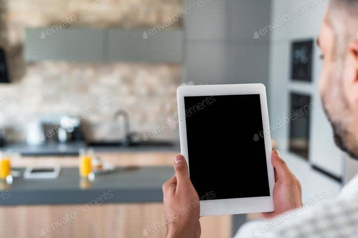 selective focus of man holding tablet with blank screen in hands in kitchen