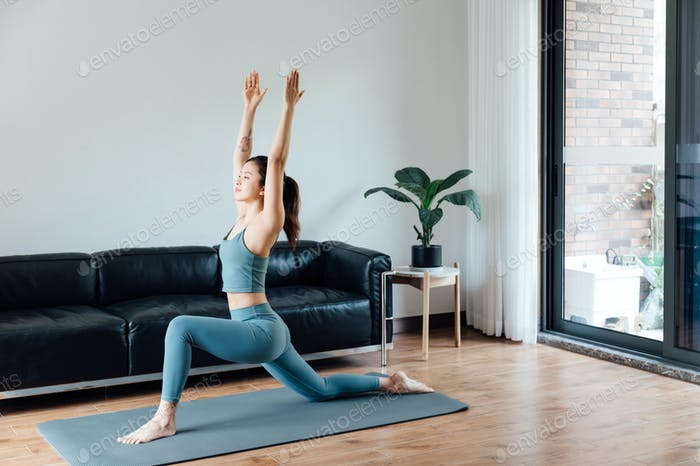 Junge asiatische Frau macht Yoga drinnen