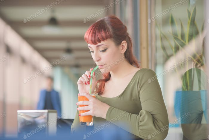 young handsome redhead woman drinking juice
