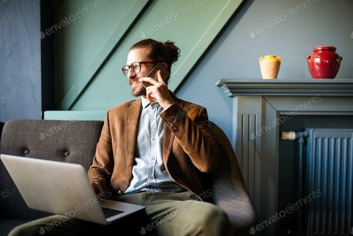 Hombre de negocios joven que trabaja, relajarse en el sofá con una computadora portátil