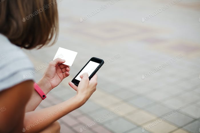 Woman using phone and card for shopping
