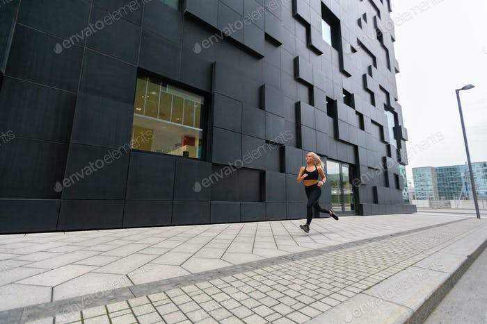 Fit woman in sports top running in modern city environment
