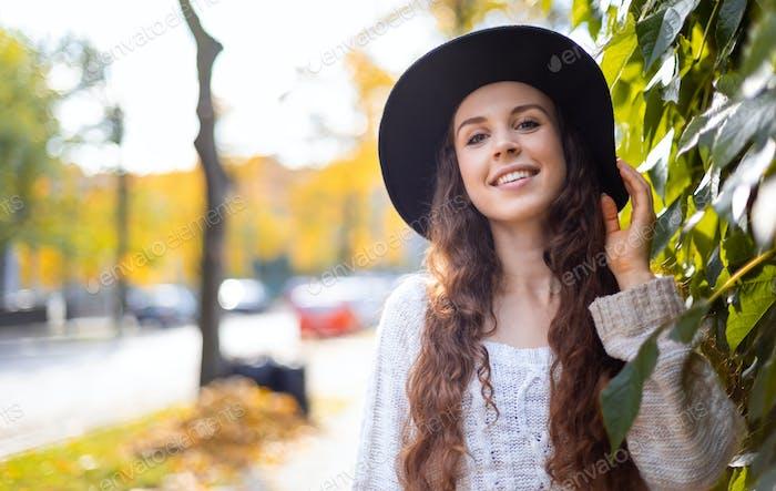 Young woman walking outdoors in autumn enjoying weather