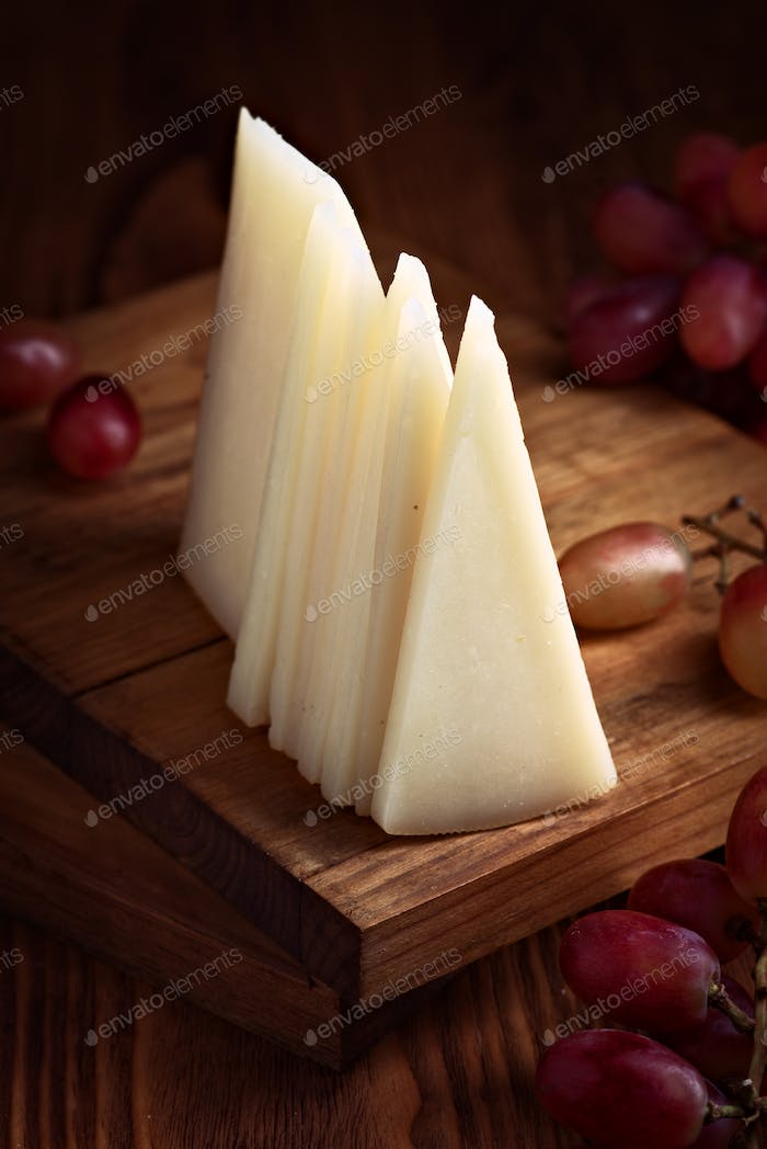 portions of spanish cheese on wood with selective light