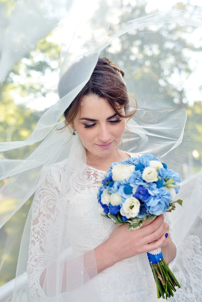 Schönheit Braut im Brautkleid mit Blumenstrauß und Spitze Schleier in der Natur