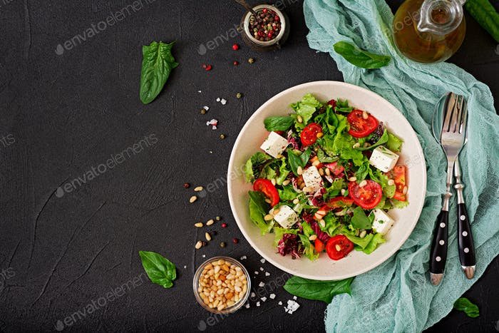 Dietary salad with tomatoes, feta, lettuce, spinach and pine nuts. Top view. Flat lay.
