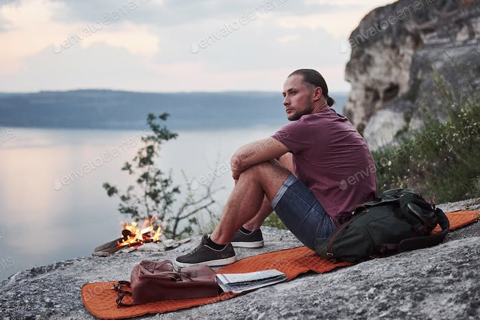 Successful man hiker on top of rock with campfire