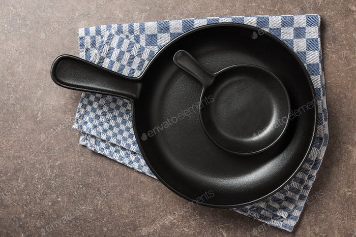 Big and small frying pans on kitchen table