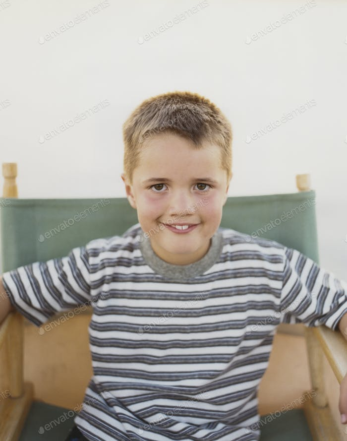 A confident boy sitting in a folding director's chair, smiling a toothy smile.