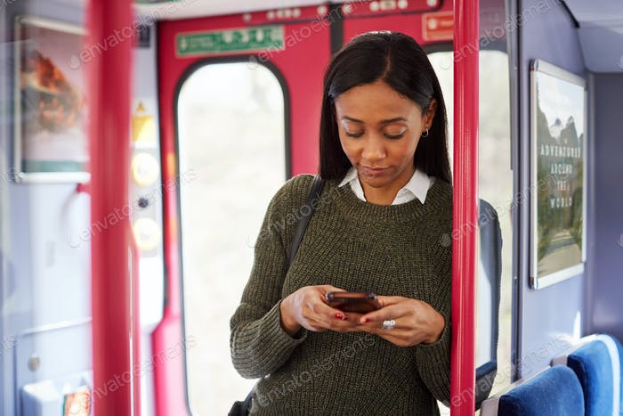 Female Passenger Standing By Doors In Train Looking At Mobile Phone