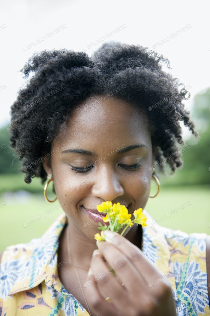 Portrait of a woman holding a yellow flower.