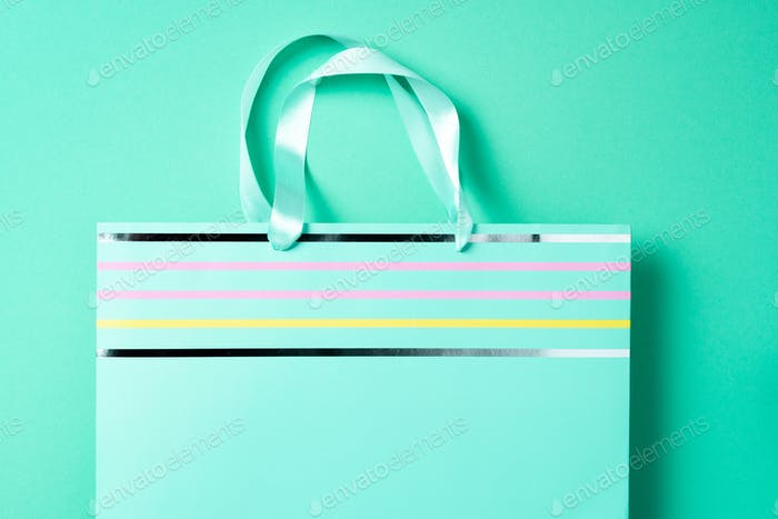 Turquoise paper shopping bag on trendy green background. Top view, copy space. Gift concept. Woman