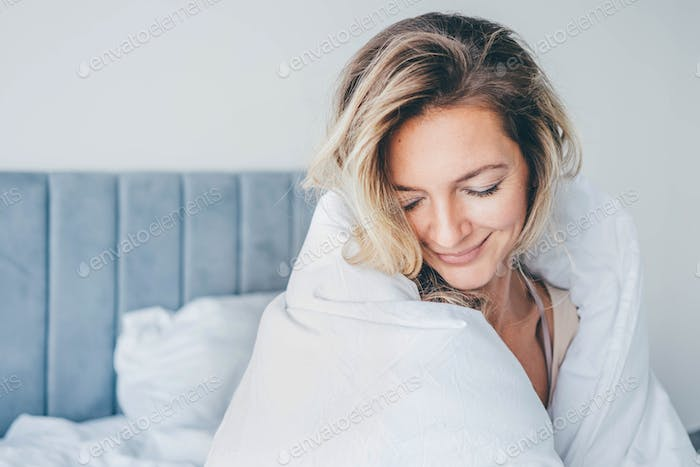 Woman with long fair hair covers with large blanket sitting on bed in morning