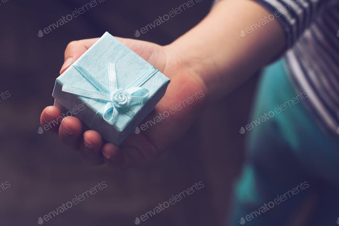kid holding a small blue gift box with ribbon in his hand