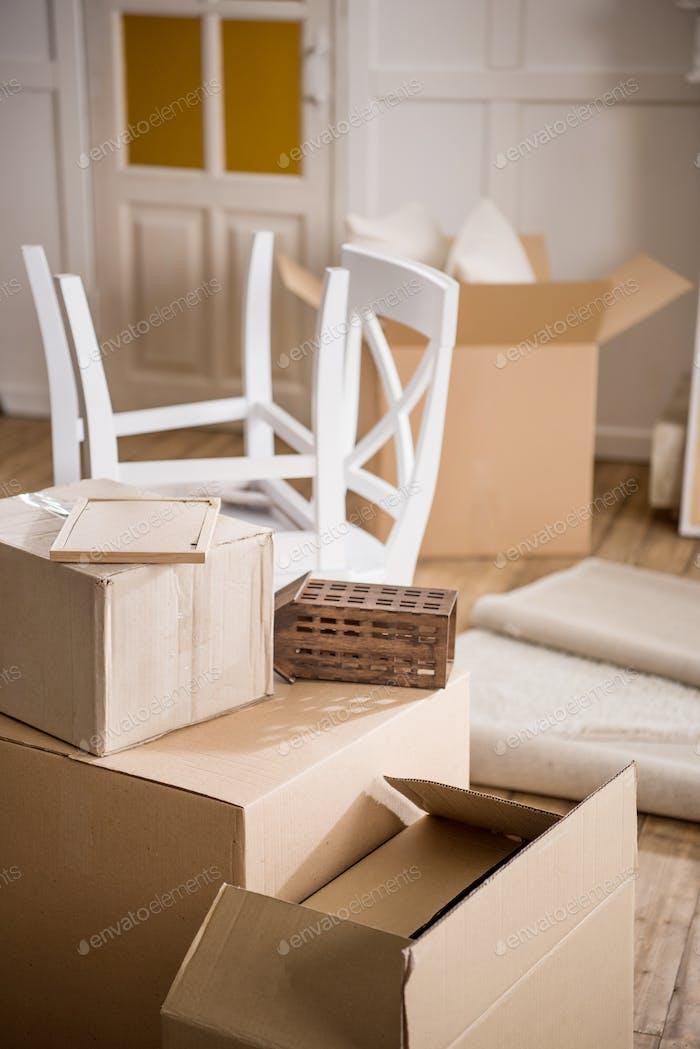 Cajas de cartón y muebles en habitación vacía, concepto de reubicación