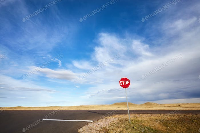 Desert highway with a stop sign, concept picture, USA