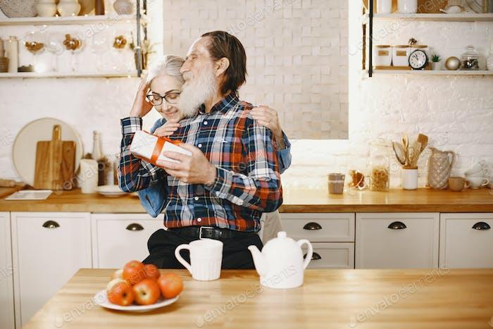 Seniorenpaar mit Geschenken in einer Küche