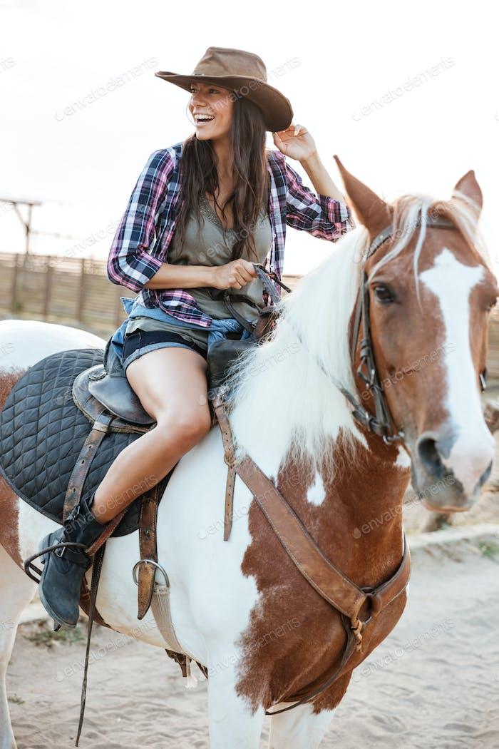 Fröhlich Frau Cowgirl sitzend und Reiten Pferd in Dorf