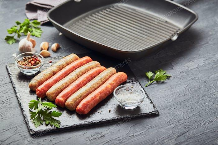 Rohe Fleischwürste auf einem Schieferbrett, mit Kräutern und Gewürzen und einer quadratischen Grillpfanne. Blick von oben